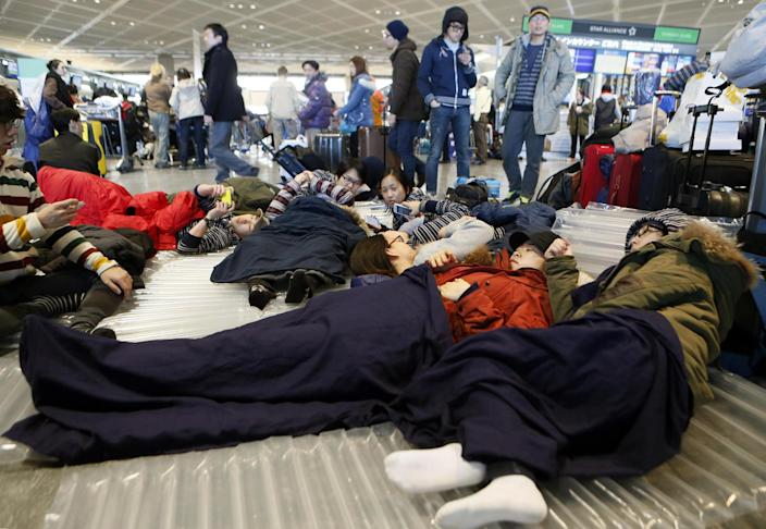 Travelers take a rest on a floor at departure lobby at Narita airport in Narita, near Tokyo Tuesday, Jan. 15, 2013 as they stayed overnight due to heavy snow. This winter's first snow in Tokyo on Monday severely disrupted train services, canceled flights and stranded tourists. (AP Photo/Kyodo News) JAPAN OUT, MANDATORY CREDIT, NO LICENSING IN CHINA, HONG KONG, JAPAN, SOUTH KOREA AND FRANCE