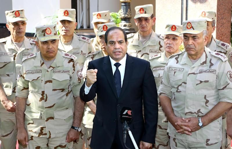 A picture released on October 25, 2014 by the Egyptian Presidency shows President Abdel Fattah al-Sisi (C), surrounded by top military generals, addressing journalists in Cairo (AFP Photo/)