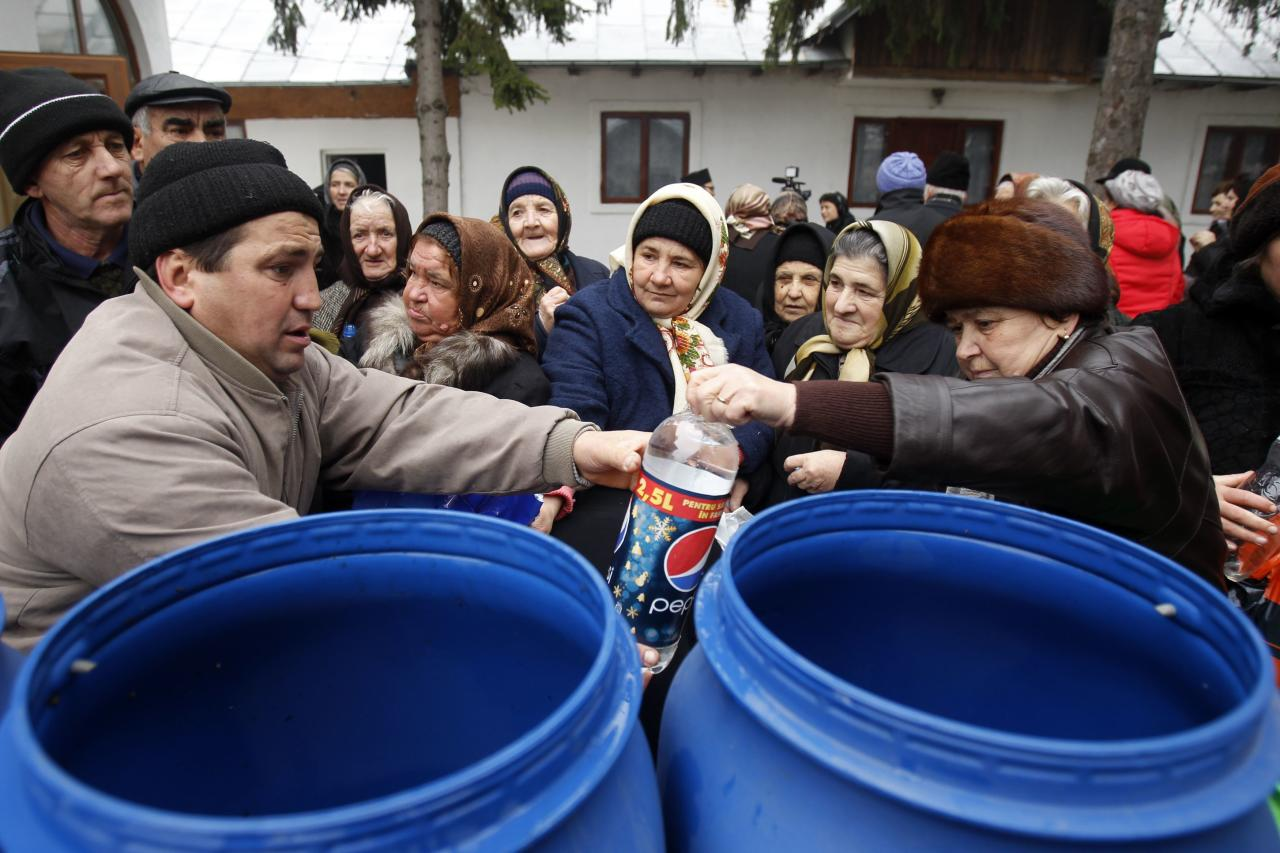 Orthodox believers take the holy water at a church on Epiphany Day in the Romanian village of Pietrosani, 45 km (28 miles) north of Bucharest, January 6, 2014. Epiphany Day falls on January 6 every year and it celebrates the end of Christmas festivities in Romania. REUTERS/Bogdan Cristel (ROMANIA - Tags: SOCIETY RELIGION)