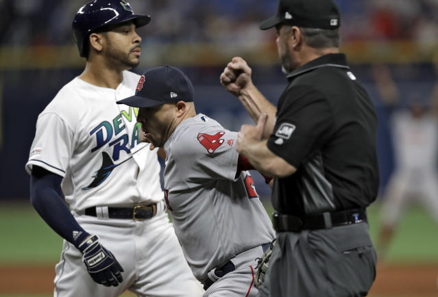 Boston Red Sox first baseman Steve Pearce, center, tags out Tampa Bay Rays' Tommy Pham, left, at first on a pickoff play during the ninth inning of a baseball game Saturday, April 20, 2019, in St. Petersburg, Fla. Making the call is umpire Rob Drake. (AP Photo/Chris O'Meara)