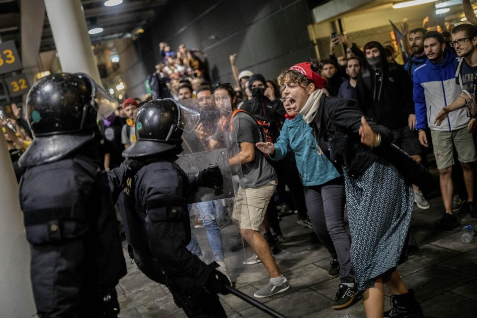 Police scuffle with protesters during a demonstration at El Prat airport, outskirts of Barcelona, Spain, Monday, Oct. 14, 2019. Spain's Supreme Court on Monday sentenced 12 prominent former Catalan politicians and activists to lengthly prison terms for their roles in a 2017 bid to gain Catalonia's independence, sparking protests across the wealthy Spanish region. (AP Photo/Bernat Armangue)