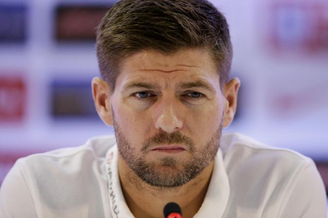 FILE - In this Sunday, June 22, 2014 file photo, England national soccer team captain Steven Gerrard listens as head coach Roy Hodgson speaks during a press conference after a squad training session that was closed to the media for the 2014 soccer World Cup at the Urca military base in Rio de Janeiro, Brazil. England captain Steven Gerrard announced his retirement from international football on Monday, July 21, 2014. The 34-year-old Liverpool midfielder made 114 appearances for England over 14 years. (AP Photo/Matt Dunham, File)