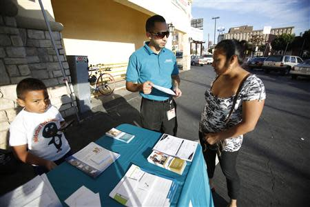 Jaime Corona, patient care coordinator at AltaMed, speaks to a woman during a community outreach on Obamacare in Los Angeles, California November 6, 2013. REUTERS/Mario Anzuoni