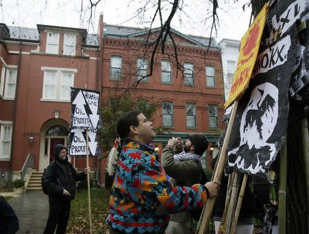 Wica Agli, a member group in the Cowboy Indian alliance, co-founder Aldo Seoane (C), gathers protest signs against the Keystone XL pipeline in front of the home of U.S. Senator Mary Landrieu (D-LA), chair of the Senate Energy Committee, in in Washington November 17, 2014.   REUTERS/Gary Cameron