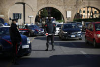 Carabinieri police officers check veichles at a road block , in Rome, Monday, March 15, 2021. Half of Italy's regions have gone into the strictest form of lockdown in a bid to curb the latest spike in coronavirus infections that have brought COVID-19 hospital admissions beyond manageable thresholds. (Cecilia Fabiano/LaPresse via AP)