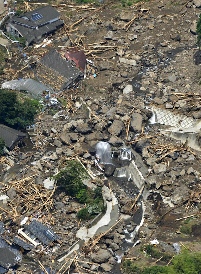 Houses are buried in a landslide in Aso, Kumamoto Prefecture, Japan, Sunday, July 15, 2012. Heavy rain triggered flash floods and mudslides in southern Japan this week, killing over two dozens of people. (AP Photo/Kyodo News) JAPAN OUT, MANDATORY CREDIT, NO LICENSING IN JAPAN, CHINA, HONG KONG, SOUTH KOREA AND FRANCE