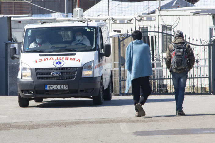 An ambulance exits the Miral migrant camp, in Velika Kladusa, Bosnia, Wednesday, April 7, 2021. Bosnia is seeing a rise in coronavirus infections among migrants and refugees living in its camps, as it struggles to cope with one of the Balkans' highest COVID-19 death and infection rates among the general population.(AP Photo/Davor Midzic)