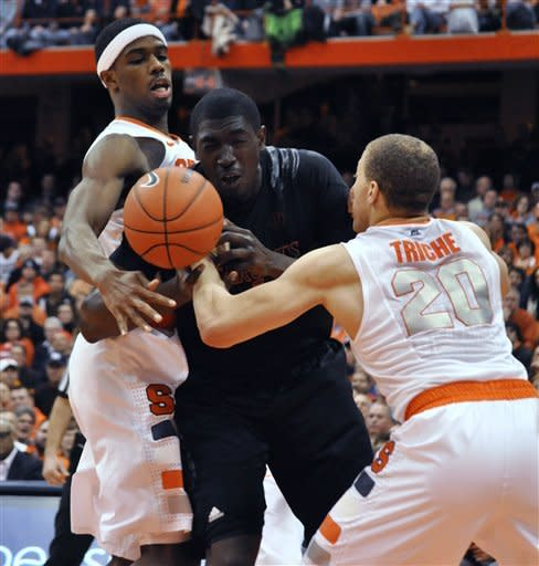 Cincinnati's Cheikh Mbodj works between Syracuse's C. J. Fair, rear, and Brandon Triche for a loose ball during the second half of an NCAA college basketball game in Syracuse, N.Y., Monday, Jan. 21, 2013. Syracuse won 57-55. (AP Photo/Kevin Rivoli)