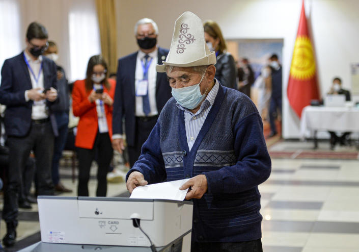 A man in a Kyrgyz national hat casts his ballot at a polling station during the referendum in Bishkek, Kyrgyzstan, Sunday, April 11, 2021. Voters in Kyrgyzstan cast ballots Sunday on whether to approve a new constitution that would substantially increase the president's powers. The Sunday referendum comes three months after Sadyr Zhaparov was elected president, following the ouster of the previous president amid protests, the third time in 15 years that a leader of the Central Asian country had been driven from office in a popular uprising. (AP Photo/Vladimir Voronin)