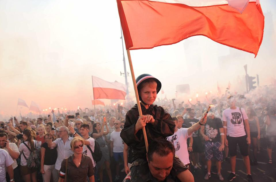 <p>Residents of Warsaw gathered in city center to pay tribute for the victims of Warsaw Uprising. (Rex features) </p>