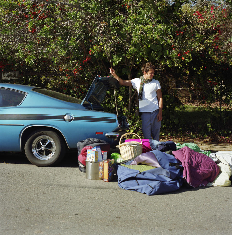 Man with luggage next to car. Source: Getty Images