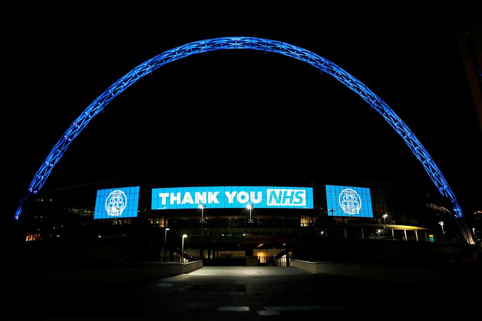 Wembley stadium is seen lit up blue for the Clap For Our Carers campaign in support of the NHS during the coronavirus pandemic in March (Photo: Matthew Childs / Reuters)