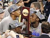 Kentucky forward Anthony Davis, left, and forward Michael Kidd-Gilchrist, right, kiss the trophy after the NCAA Final Four tournament college basketball championship game Tuesday, April 3, 2012, in New Orleans. Kentucky beat Kansas 67-59. (AP Photo/Bill Haber)
