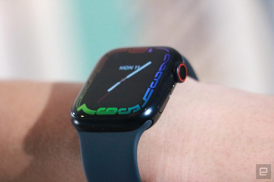 An off-angle view of the Apple Watch Series 7 on a person's wrist, showing the screen's refracted edge and the watch's dial and button.