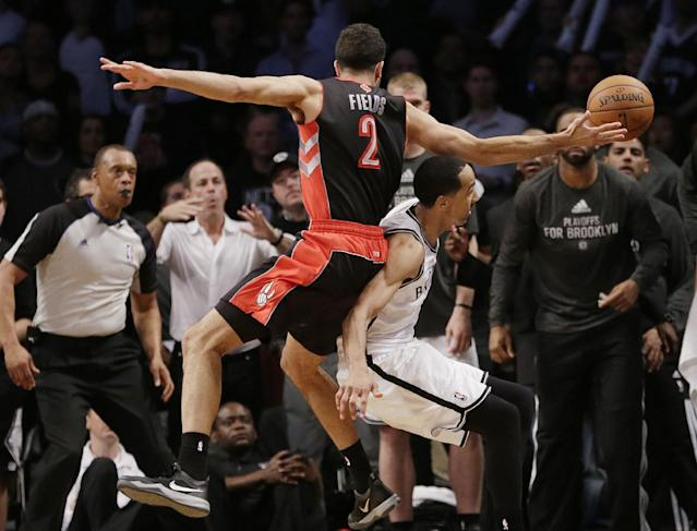 Toronto Raptors' Landry Fields, above, falls over Brooklyn Nets' Shaun Livingston, below as he chased a ball out of bounds during the second half of Game 3 of an NBA basketball first-round playoff series Friday, April 25, 2014, in New York. The Nets won 102-98. (AP Photo/Frank Franklin II)