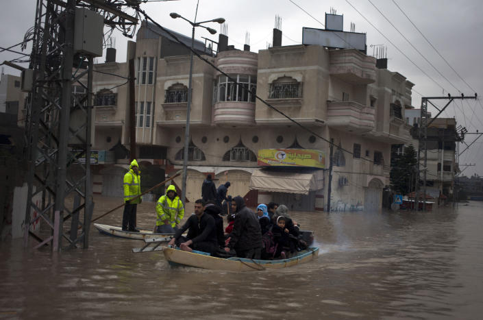 Palestinian rescue members evacuate residents using a fishing boat following heavy rains in Gaza City, Saturday, Dec. 14, 2013. Rescue workers evacuated more than 5,000 Gaza Strip residents from homes flooded by four days of heavy rain, using fishing boats and heavy construction equipment to pluck some of those trapped from upper floors, an official said Saturday. (AP Photo/Khalil Hamra)