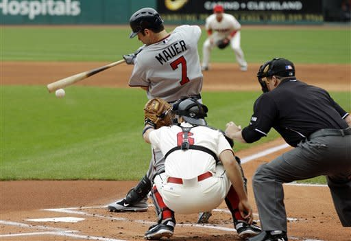 Minnesota Twins' Joe Mauer (7) singles to drive in a run in the first inning of a baseball game against the Cleveland Indians, Sunday, June 3, 2012, in Cleveland. Indians catcher Lou Marson (6) and umpire Marty Foster watch the play. (AP Photo/Mark Duncan)