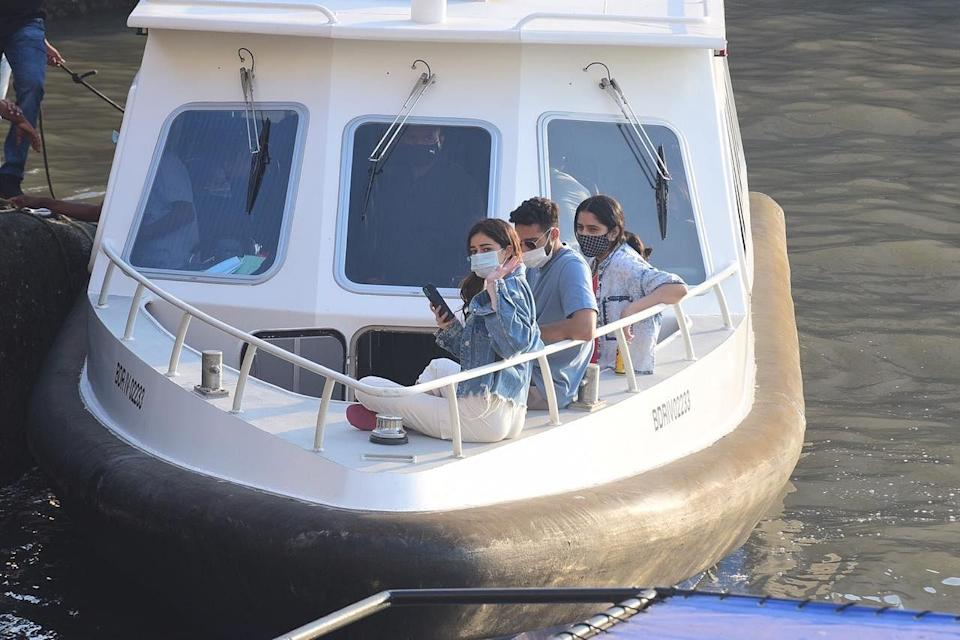 Ananya Panday waves to the paps from the boat.