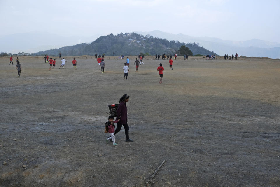 A Tangkhul Naga woman holds the hand of a child and walks past boys engaged in a friendly soccer match, with Nungshang village seen on the mountaintop, in Shangshak village, in the northeastern Indian state of Manipur, Saturday, Jan. 30 2021. Most Naga villages are perched on mountaintops, originally built long ago to spot approaching enemies when the region was little more than a forest. But on nearly every mountaintop, there will be a flat rectangle to serve as a soccer field. (AP Photo/Yirmiyan Arthur)
