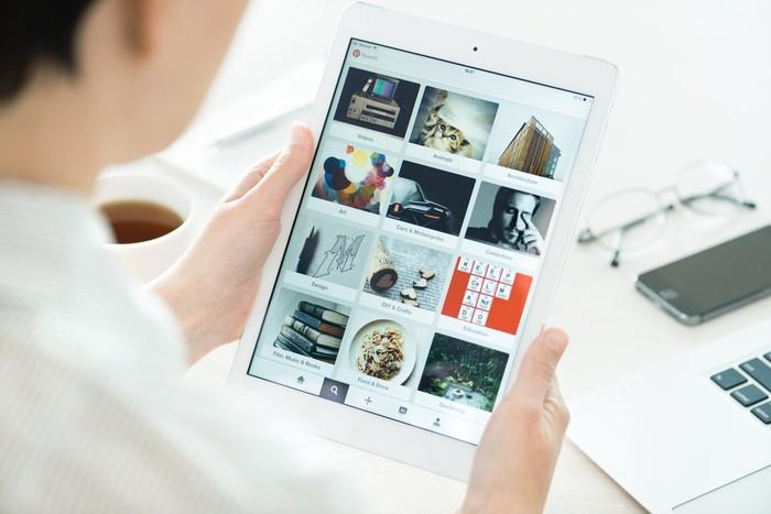 Woman browsing Pinterest's platform using a white Apple iPad.