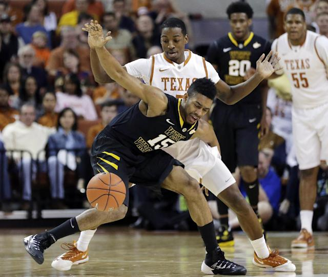 West Virginia's Terry Henderson (15) is pressured by Texas' Damarcus Croaker during the first half of an NCAA college basketball game, Saturday, Feb. 15, 2014, in Austin, Texas. (AP Photo/Eric Gay)