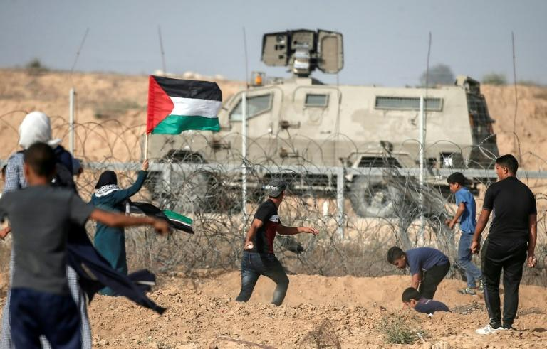 Palestinian demonstrators throw stones at Israeli security forces during protests along the border with Israel east of Khan Yunis, in the southern Gaza Strip