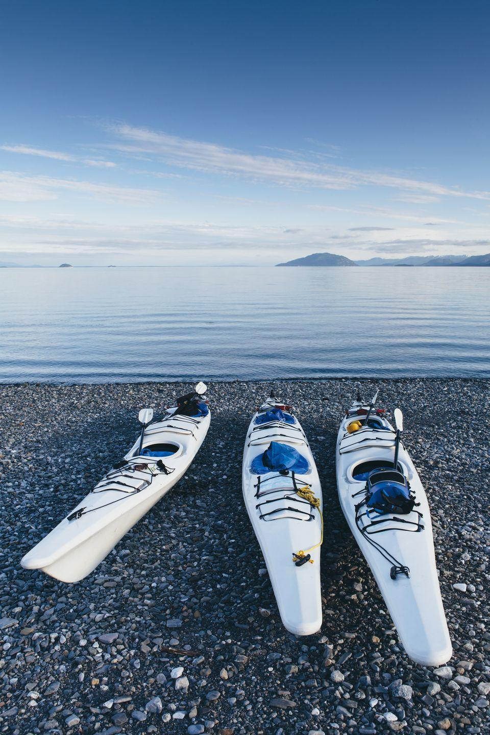 <p>Kayaks on a remote beach along the Muir Inlet in Alaska, overlooking Glacier Bay National Park in the distance.</p>