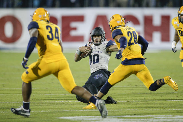 Utah State quarterback Jordan Love (10) slides as Kent State linebackers Kesean Gamble (34) and Mandela Lawrence-Burke (28) defend during the first half of the Frisco Bowl NCAA college football game Friday, Dec. 20, 2019, in Frisco, Texas. (AP Photo/Brandon Wade)