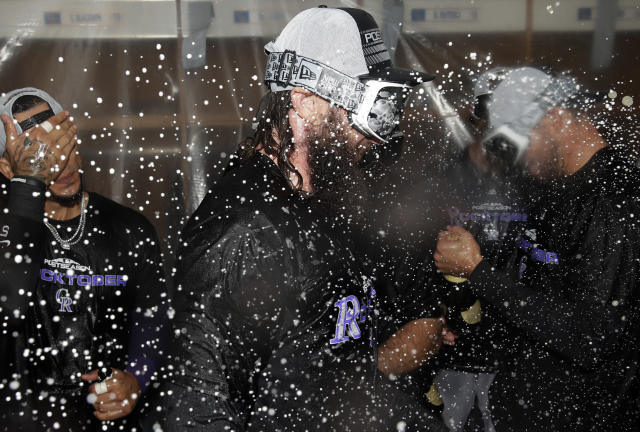 Colorado Rockies' Charlie Blackmon celebrates with teammates in the club house after defeating the Chicago Cubs 2-1 in the National League wild-card playoff baseball game early Wednesday, Oct. 3, 2018, in Chicago. (AP Photo/Nam Y. Huh)