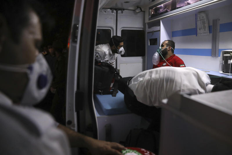 A rescue worker receives oxygen in an ambulance after he was overcome by smoke from the explosion of Sina Athar Clinic in Tehran, Iran, early Wednesday, July 1, 2020. Iranian state TV says an explosion from a gas leak in a medical clinic in northern Tehran has killed multiple people. (AP Photo/Vahid Salemi)