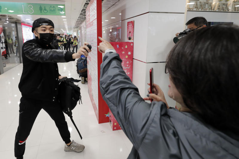 "A woman gestures as an undercover policeman points a can of pepper spray during a demonstration at a shopping mall popular with traders from mainland China near the Chinese border in Hong Kong, Saturday, Dec. 28, 2019. Protesters shouting ""Liberate Hong Kong!"" marched through a shopping mall Saturday to demand that mainland Chinese traders leave the territory in a fresh weekend of anti-government tension. (AP Photo/Lee Jin-man)"