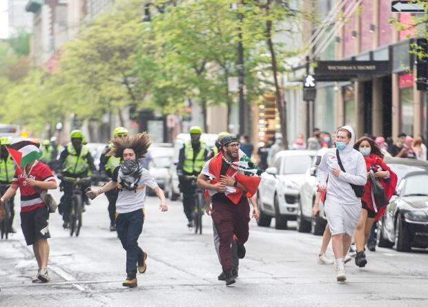 Pro-Palestinian demonstrators run from police following a demonstration in Montreal on Sunday. (Graham Hughes/The Canadian Press - image credit)