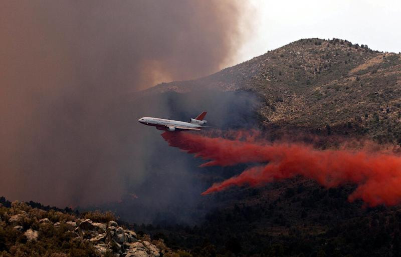 Tanker 910 makes a retardant drop on the Yarnell Hill Fire to help protect the Double Bar A Ranch near Peeples Valley, Arizona, Sunday, June 30, 2013. The lightning caused blaze began on Yarnell Hill on Sunday. (AP Photo/The Arizona Republic, Tom Story)