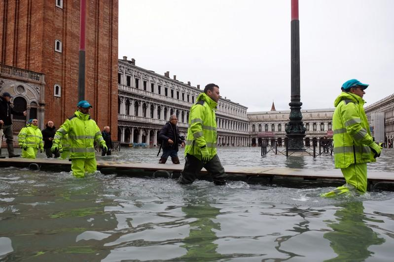 Workers walk in St. Mark's Square after days of severe flooding in Venice