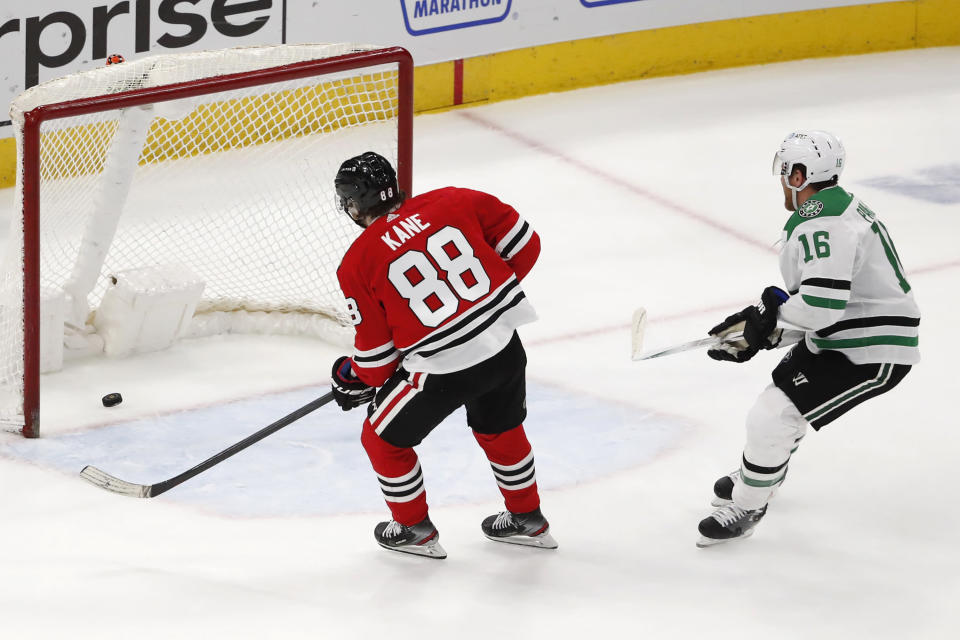 Chicago Blackhawks right wing Patrick Kane (88) scores an empty net goal as Dallas Stars center Joe Pavelski (16) looks on during the third period of an NHL hockey game Tuesday, April 6, 2021, in Chicago. The Blackhawks won the game 4-2. (AP Photo/Jeff Haynes)