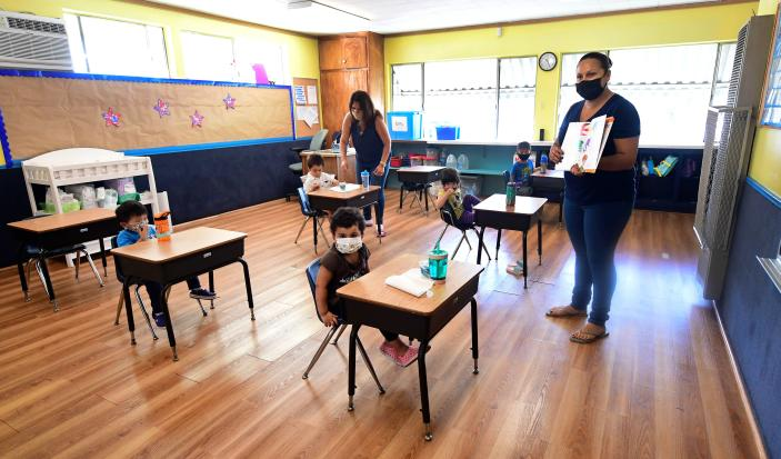 Instructor Chablis Torres reads to preschoolers, wearing masks and spaced appropriately apart as per coronavirus guidelines, during summer school sessions in Monterey Park, Calif., on July 9. (Frederic J. Brown/AFP via Getty Images)