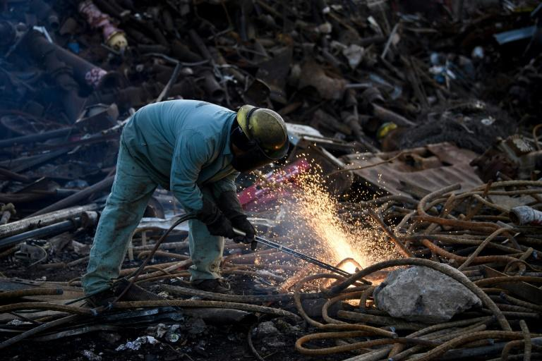 A worker at Josh Steel Company cuts scrapped steel rebar for recycling in North Braddock, Pennsylvania -- a key electoral state where the industry has had a far-reaching impact