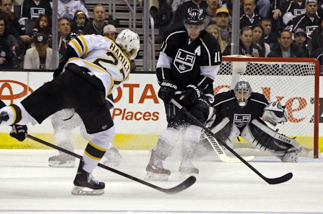 Boston Bruins defenseman Dougie Hamilton (27) shoots as Los Angeles Kings center Anze Kopitar (11), of Yugoslavia, and goalie Jonathan Quick (32) in the second period of an NHL hockey game in Los Angeles Thursday, Jan. 9, 2014. (AP Photo/Reed Saxon)
