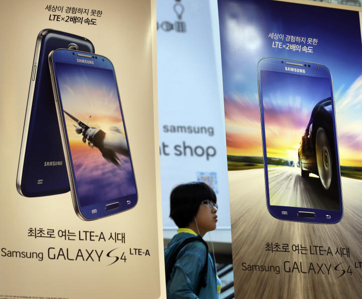 A visitor stands near the billboards of Samsung Electronics' Galaxy S4 smart phones at a showroom of its headquarters in Seoul, South Korea, Friday, July 26, 2013. Samsung Electronics reported a record-high profit for a sixth straight quarter but still disappointed investors who had higher expectations for the world's largest smartphone maker. (AP Photo/Lee Jin-man)