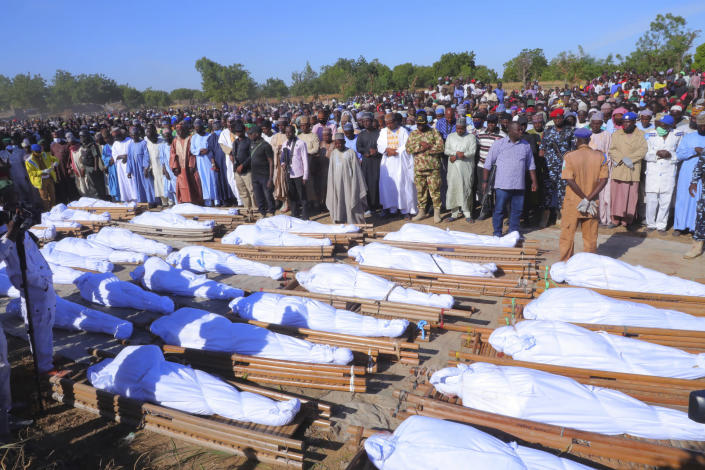 People attend a funeral for those killed by suspected Boko Haram militants in Zaabarmar, Nigeria, Sunday, Nov. 29, 2020. Nigerian officials say suspected members of the Islamic militant group Boko Haram have killed at least 40 rice farmers and fishermen while they were harvesting crops in northern Borno State. The attack was staged Saturday in a rice field in Garin Kwashebe, a Borno community known for rice farming. (AP Photo/Jossy Ola)