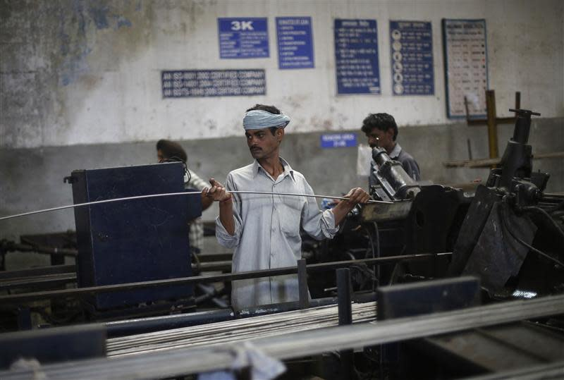 An employee holds a steel rod as he works on the production line inside Hallmark steel factory in Bhiwadi