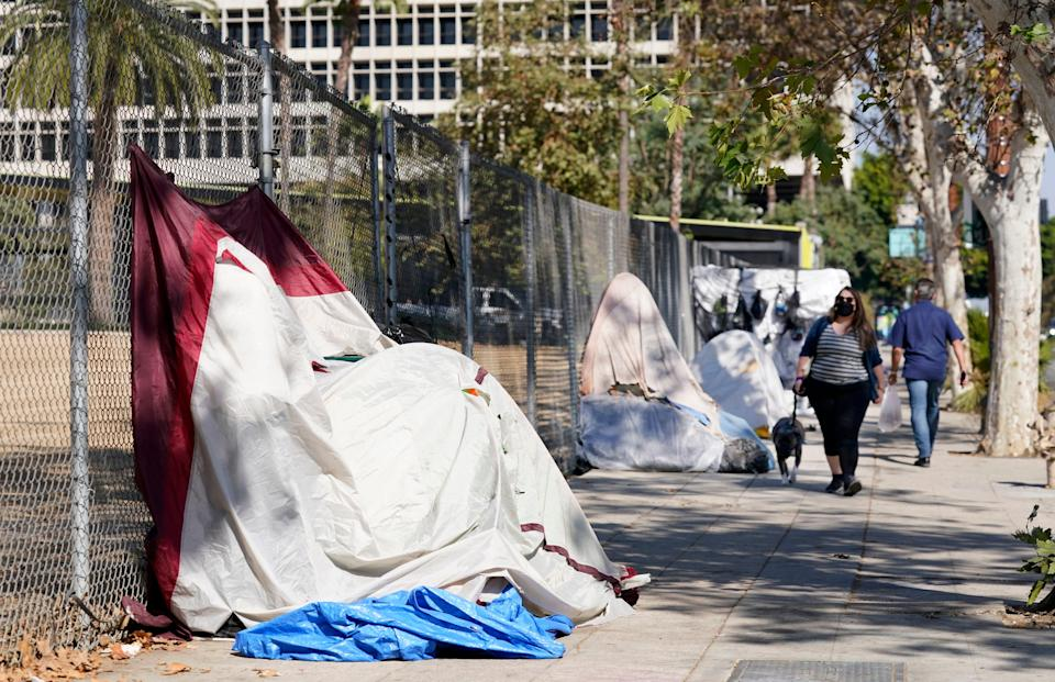 Pedestrians walk past a homeless encampment just outside Grand Park on Wednesday in Los Angeles.