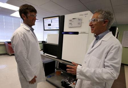 Alan Shuldiner (R) and Aris Baras, co-heads of the Regeneron Genetics Center, stand near genetic sequencing machines at a Regeneron Pharmaceuticals Inc. laboratory at the biotechnology company's headquarters in Tarrytown, New York March 24, 2015. REUTERS/Mike Segar