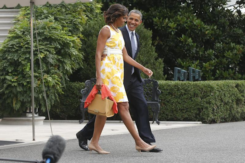 President Barack Obama and first lady Michelle Obama walk towards the South Lawn at the White House in Washington, Saturday, Aug. 10, 2013, as they travel to Orlando, Fla. before heading to their vacation in Martha's Vineyard. (AP Photo/Charles Dharapak)