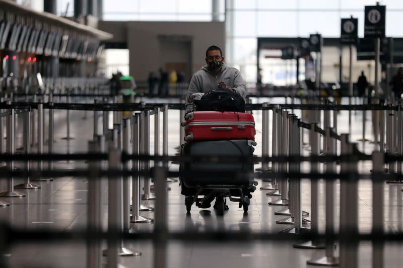FILE PHOTO: A passenger wearing a protective mask carries his luggage at the El Dorado International Airport, in Bogota