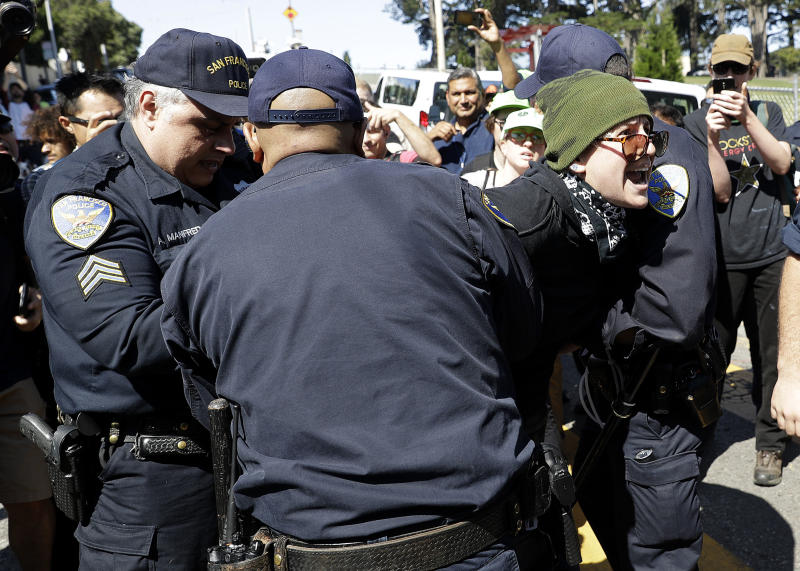 San Francisco Police Officers arrest a protester outside of Alamo Square Park in San Francisco, Saturday, Aug. 26, 2017. San Francisco officials took further steps Saturday to prevent violence ahead of a planned news conference by a right-wing group. Officials erected fencing and a large contingent of police monitored Alamo Square park, where the group Patriot Prayer was set to hold its event. (AP Photo/Marcio Jose Sanchez)