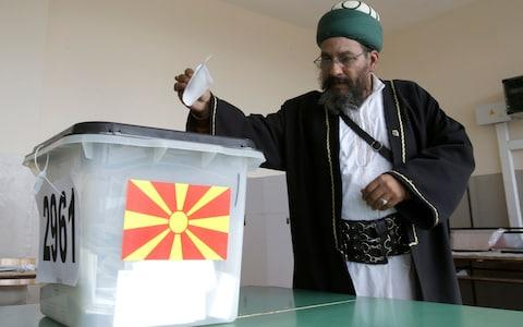 A Muslim cleric casts his ballot at polling station during the referendum in Skopje, Macedonia - Credit: Boris Grdanoski/AP