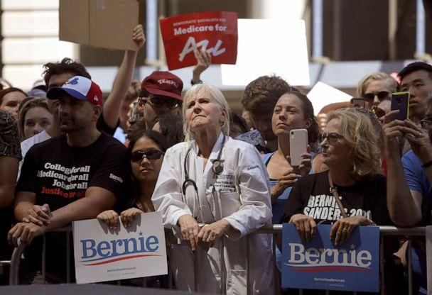 PHOTO: Dr. Rene Rubin listens to Democratic presidential candidate Bernie Sanders, make remarks at a rally alongside unions, hospital workers and community members against the closure of Hahnemann University Hospital in Philadelphia, July 15, 2019. (Jacqueline Larma/AP)
