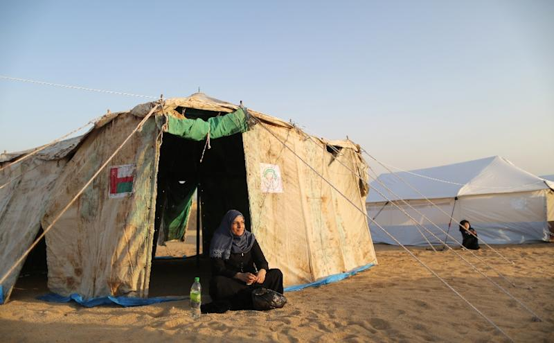 A woman sits outside a tent at a Palestinian protest camp near Gaza's border with Israel on March 29, 2018 (AFP Photo/MAHMUD HAMS)