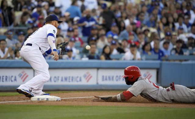 St. Louis Cardinals' Dexter Fowler, right, dives into third as Los Angeles Dodgers third baseman Justin Turner takes a late throw after Paul Goldschmidt flied out during the first inning of a baseball game Tuesday, Aug. 6, 2019, in Los Angeles. (AP Photo/Mark J. Terrill)